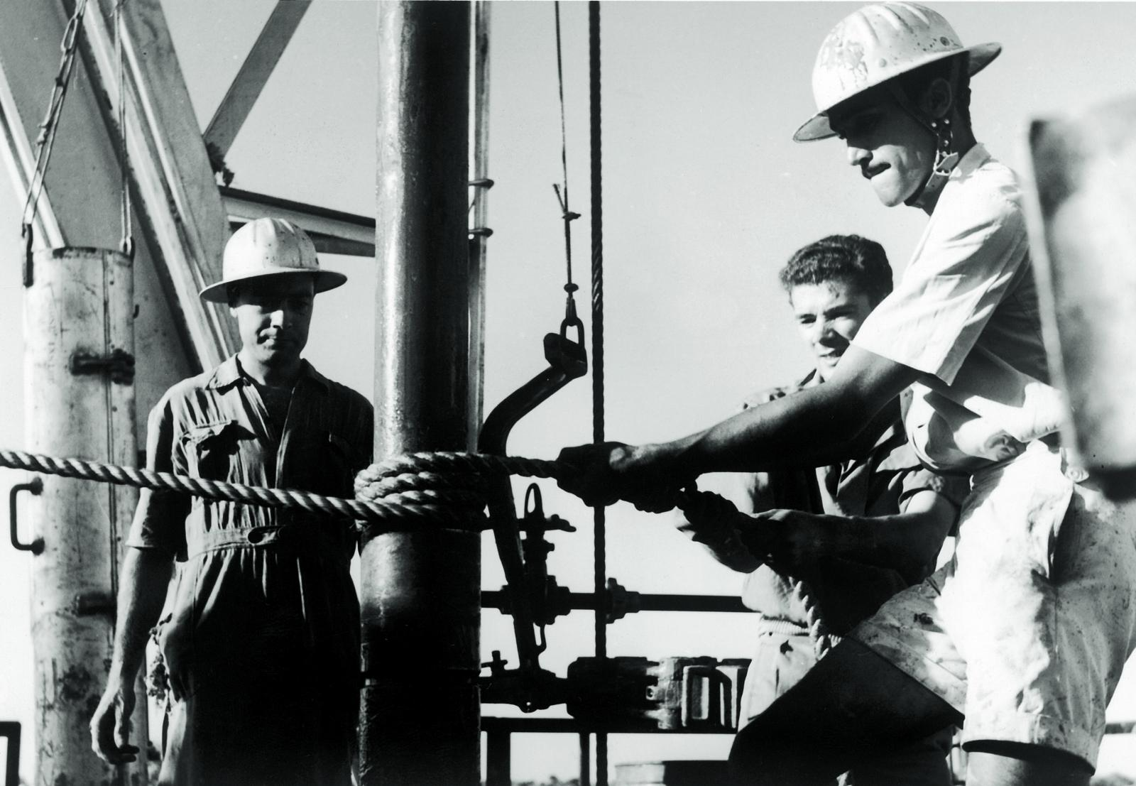 In those pioneering days, safety requirements were vastly different from today's standards. Here, for example, drill pipes are being tightened using a rope – a technique that cost several drillers their fingers – and samples are being taken at the wellhead.